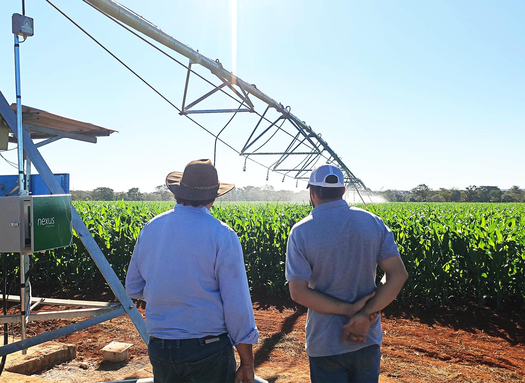 Fazendeiro e revendedor observam o pivô irrigar após instalação do Nexus.